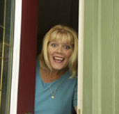 Happy woman peeking her head out the front door